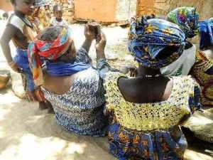 Les femmes rurales regardant une soirée de balafon sur téléphone