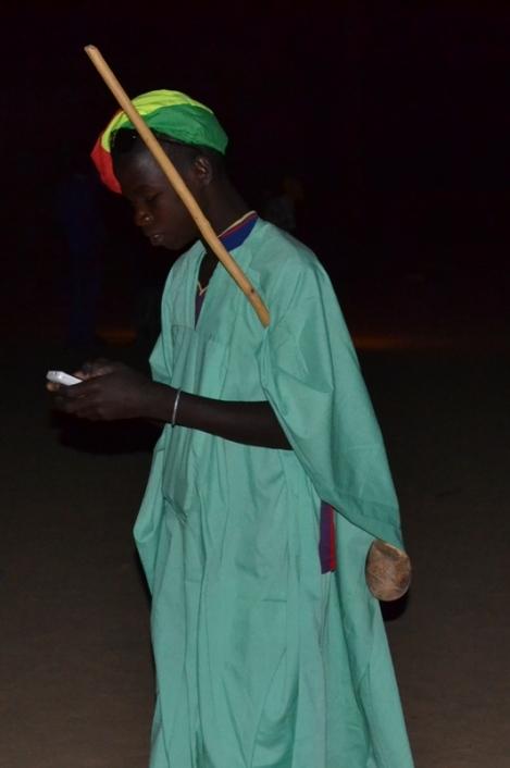 Un jeune peul avec son gourdin,  navigant sur son portable