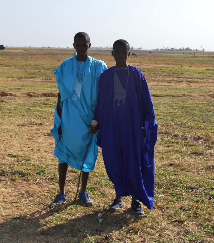 Deux jeunes peuls en tenue traditionnelle  partant sur le lieu de la cérémonie