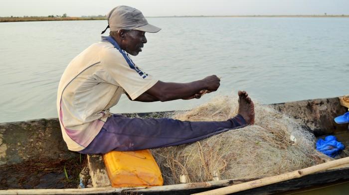 Un pêcheur réparant son filet de pêche déchiré